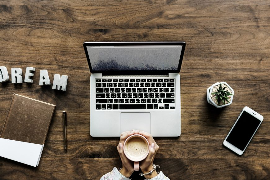 Laptop and person holding coffee